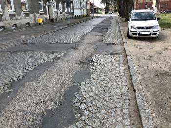 ulica Kniaziewicza przed remontem - widoczna zniszczona droga z dziurami