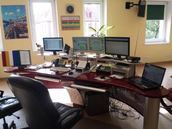 Zdjęcie biura - biurko z 5 monitorami, trzy telefony stacjonarne, dwa fotele biurowe