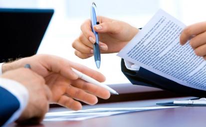 Dłonie dwóch osób. Jedna trzyma długopis i dokumenty
