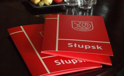 czerwone teczki z białym logiem Słupska i napisem Słupsk