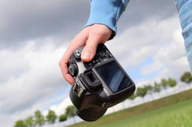 Dłoń trzymająca aparat fotograficzny