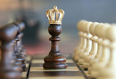 Zdjęcie szachownicy: w centrum czarny pion z ze złotą koroną, po prawej stronie rząd białych pionów, po lewej rząd czarnych pionów