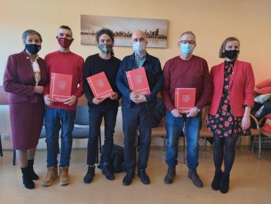 Prezydentki Krystyna Danilecka- Wojewódzka i Marta Makuch w towarzystwie czterech mężczyzn- tegorocznych stypendystów w dziedzinie kultury trzymający w dłoniach dyplomy okolicznościowe w czerwonych teczkach