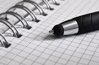 długopis leżący na kartce w kratkę