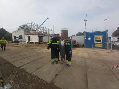 Na zdjęciu widizmy czworo ludzi -  2 mężczyzn i 2 kobiety, którzy  stoją na tle terenu budowy. W tle widać przechodzącego mężczyznę.