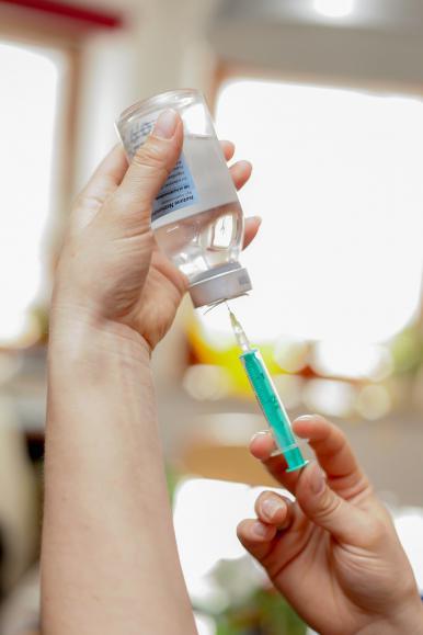 na zdjęciu widzimy szczepionkę nabieraną z fiolki do strzykawki