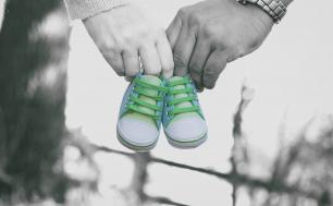 ręce kobiety i mężczyzny trzymające niemowlęce buciki