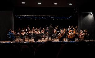 na scenie Filharmonii młodzi muzycy z instrumentami  podczas koncertu siedzą na krzesłach, tyłem  do widzów stoi dyrygent . Świąteczny nastój, światełka