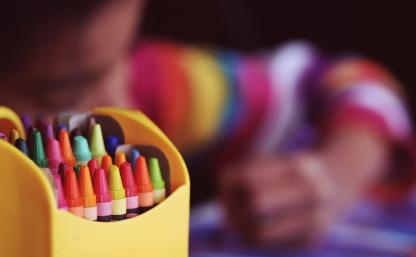 kolorowe kredki w pojemniku, w tle rysujące dziecko; Zdjęcie wykonane przez Free-Photos dla Pixabay