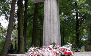 Na zdjęciu widzimy betonowy krzyż z napisem KATYŃ, przed którym znajdują się wiązanki kwiatów