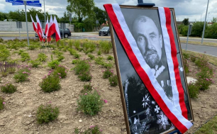 Na zdjęciu widzimy flagi Rzeczypospolitej Polskiej, tabliczki z nazwą ronda - RONDO GEN. TADEUSZA ROZWADOWSKIEGO oraz zdjęcie patrona przesłonięte szarfą w kolorach białym i czerwonym