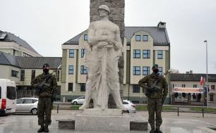 Na zdjęciu widzimy pomnik,a po jego po stronach żołnierzy w pełnym umundurowaniu z bronią. W tle kamienice, auta i flagi RP.