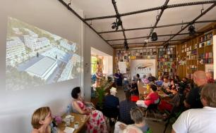 Na zdjęciu widzimy kilkanaście osób, w tle książki na półkach a na ścianie wizualizację przebudowy Starego Rynku