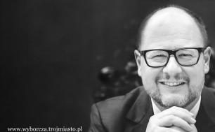 Czarno białe zdjęcie Pawła Adamowicza - mężczyzna w okularach trzymający pod broda złożone ręce