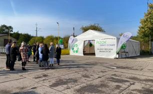 Na zdjęciu widzimy namiot, którym można zostawiać lub pobierać rzeczy; obok balony, stolik a także grupkę ludzi. W tle widać, drzewa, ogrodzenie i linie elektryczne