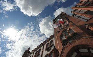zdjęcie ratusza od dołu - widoczne niebo z chmurami oraz trzy flagi - z herbem Słupska, Polski oraz Unii Europejskiej.
