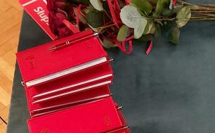 na stole leżą kalendarze z długopisami oraz bukiet róż