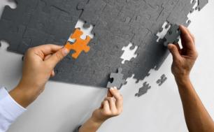 trzy ręce układające szare puzzle, jeden z puzzli jest pomarańczowy