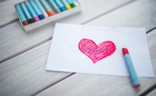 na białej kartce narsyowane czerwone serce