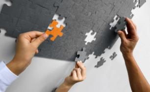 Trzy dłonie układające puzzle, jedna pomarańczowe, dwie szare.