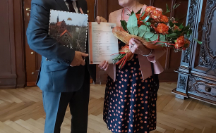Na zdjęciu widzimy kobietę i mężczyznę, elegancko ubranych, którzy się uśmiechają, trzymają skrócony odpis aktu małżeństwa, mężczyzna dodatkowo trzyma Album o Słupsku BOSZa, a kobieta kwiaty