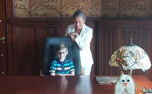 Na zdjęciu widzimy małego chłopca w okularach siedzącego w fotelu prezydenckim oraz Panią Prezydent uśmiechającą się do niego