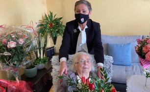 Na zdjęciu widzimy dwie kobiety - jedna siedzi na fotelu, druga stoi za nią i obejmuje ją za ramiona. Widać też dużo kwiatów, bukiety róż, tulipanów i innych pięknych kolorowych kompozycji.
