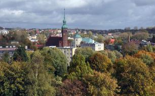 Na zdjęciu widzimy kościół św. Jacka, ceglaną budowlę ze strzelistą wieżą, oprócz tego dużo zieleni, drzew i panoramę miasta Słupska