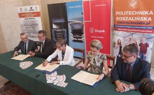 Na zdjęciu widzimy 5 osób - 2 kobiety i 3 mężczyzn, którzy podpisują dokumenty - porozumienie o współpracy. Wszystkie osoby mają okulary, na stole oprócz dokumentów znajdują się ulotki, a  za osobami podpisującymi banery z nazwami stron Porozumienia - Politechnika, Scania i Miasto Słupsk