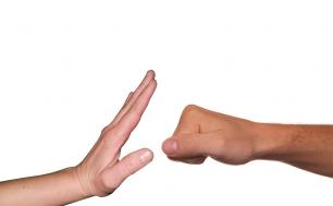 Na obrazku widzimy dwie dłonie skierowane przeciwko sobie - jedna złożona w pięść, druga rozłożona, blokująca - obrazek symbolizuje zatrzymanie agresji/przemocy