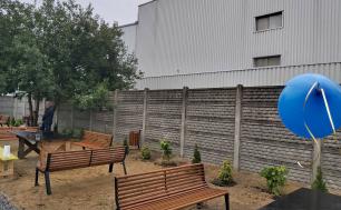 Na zdjęciwi widzimy stoły i ławki zlokalizowane na zewnątrz, zieleń, drzewa , które jako całość stanowią podwórko integracyjne dla mieszkańców.