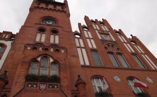 budynek ratusza, po prawej stronie flaga z herbem Słupska i flaga Polski