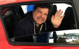Na zdjęciu widzimy ciemnowłosego mężczyzne, który ma uniesioną dłoń i macha do osób, które widzi; jest w czerwonym samochodzie, w dolnej części widzimy opuszczoną szybę i kobietę w odbiciu