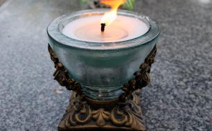 Na zdjęciu widzimy zapalony znicz w szklanej oprawie - okragły, postawiony na płaskim podłożu.