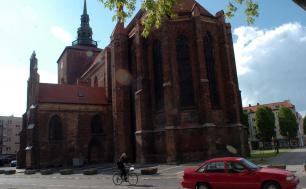 Na zdjęciu widzimy Kościół Maricacki, w tle drzewa, przed kościołem rowerzystę i zaparkowany czerwony samochód