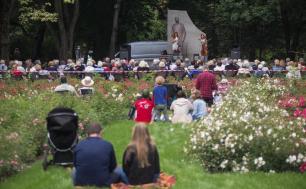 zielony park Waldorffa - uczestnicy koncertu siedzą  na trawie odwróceni na pierwszym planie dwie artystki, jedna z wiolonczela