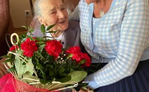 Na zdjęciu widzimy dwie kobiety, jedna siedzi na fotelu, druga, na oparciu fotela. Jubilatka ma w ręku  bukier czerwonych kwiatów, obie są uśmiechnięte i obejmują się