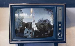 telewizor, na ekranie 5 ludzi w papierowymi torbami na głowach, w tle budynki i wieża wysokiego napięcia