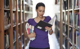 kobieta w przestrzeni bibloteki , po obu jej stronach regały z książkami. Trzyma w lewej dłoni otwartą książke, na którą patrzy, w prawej dłoni trzyma kilka książek.