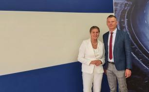 Na zdjęciu widzimy dwie osoby - kobietę i mężczyznę, Prezydentkę Miasta Słupska i Dyrektora jednostki biznesowej Stakoo, w tle logo STAKO; oboje się uśmiechają.