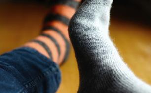 Na zdjęciu widzimy dwie stopy ubrane w różne skarpetki