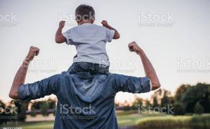 mężczyzna z dzieckem na ramionach unoszący ręce do góry