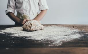 stół obsypany mąką, ciasto, w tle kucharz w białym fartuchu