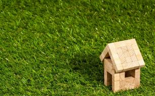 grafika prezentująca mały domek złożony z drewnianych klocków stojący na trawie